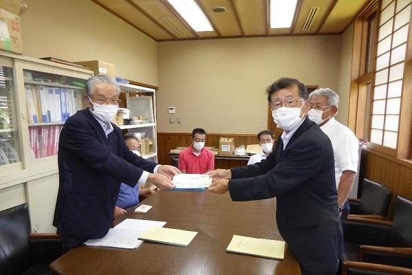 株券の授与を行う山村誠示社長(左)と美濃羽治樹理事長(右)